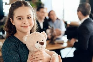 Happy,little,girl,is,hugging,teddy,bear,at,office,of